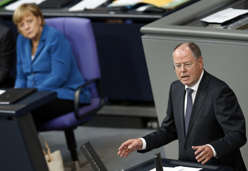 German Chancellor Angela Merkel, left, listens to the speech of Germany's Social Democratic Party (SPD) candidate for chancellor, Peer Steinbrueck, during a meeting of the German federal parliament, Bundestag, in Berlin, Germany, Tuesday, Sept. 3, 2013. (AP Photo/Michael Sohn)