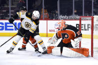 Philadelphia Flyers goaltender Brian Elliott, right, makes a save on a shot attempt by Boston Bruins' Nick Ritchie as Flyers' Robert Hagg, rear, defends during the second period of an NHL hockey game, Saturday, April 10, 2021, in Philadelphia. (AP Photo/Derik Hamilton)