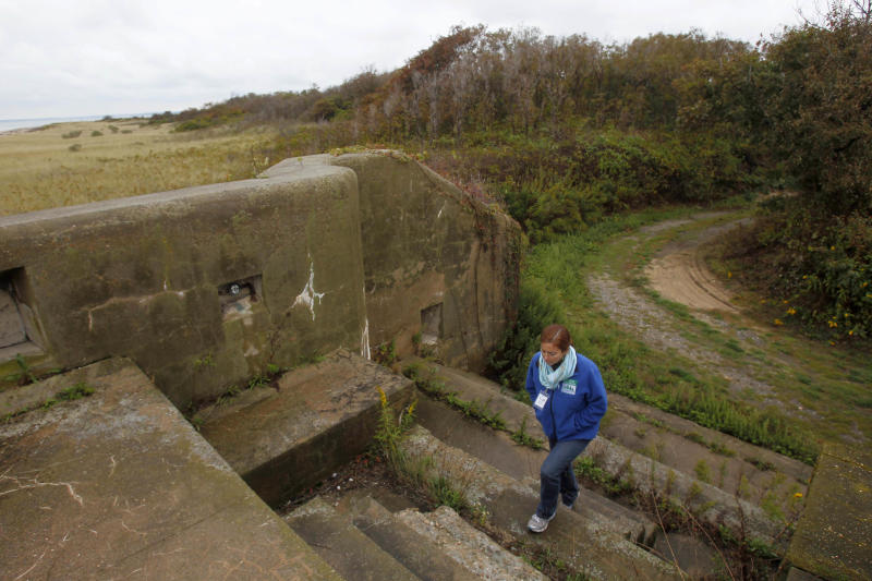 FILE - In this Oct. 6, 2013 file photo, Adrienne Esposito, director of Citizens Campaign for the Environment, walks to the top of an old battery, previously used for defense, on Plum Island in New York. Environmental groups on both sides of Long Island Sound have for several years called for the property to be kept as a nature preserve, but the government hopes to sell the island using proceeds from the sale to defray the costs of moving its research operations on the island to a new laboratory at Kansas State University. (AP Photo/Seth Wenig, File)