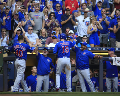 Chicago Cubs' Ben Zobrist, center, celebrates his two-run home run against the Milwaukee Brewers as he enters the dugout during the seventh inning of an baseball game Sunday, Sept. 24, 2017, in Milwaukee. (AP Photo/Darren Hauck)