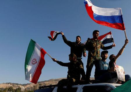 FILE PHOTO: Syrians wave Iranian, Russian and Syrian flags during a protest against U.S.-led air strikes in Damascus, Syria April 14, 2018. REUTERS/Omar Sanadiki