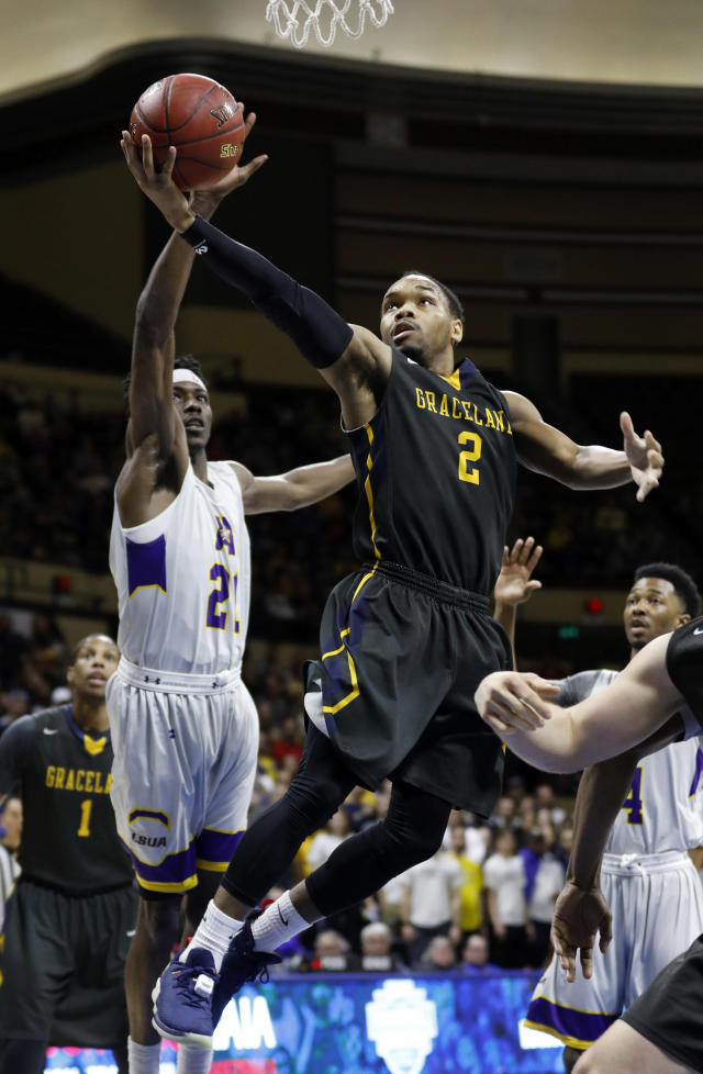 Graceland guard LT Davis (2) attempts to score against LSU Alexandria forward Brandon Moss (21) during the first half of the NAIA men's championship college basketball game Tuesday, March 20, 2018, in Kansas City, Mo. (AP Photo/Colin E. Braley)