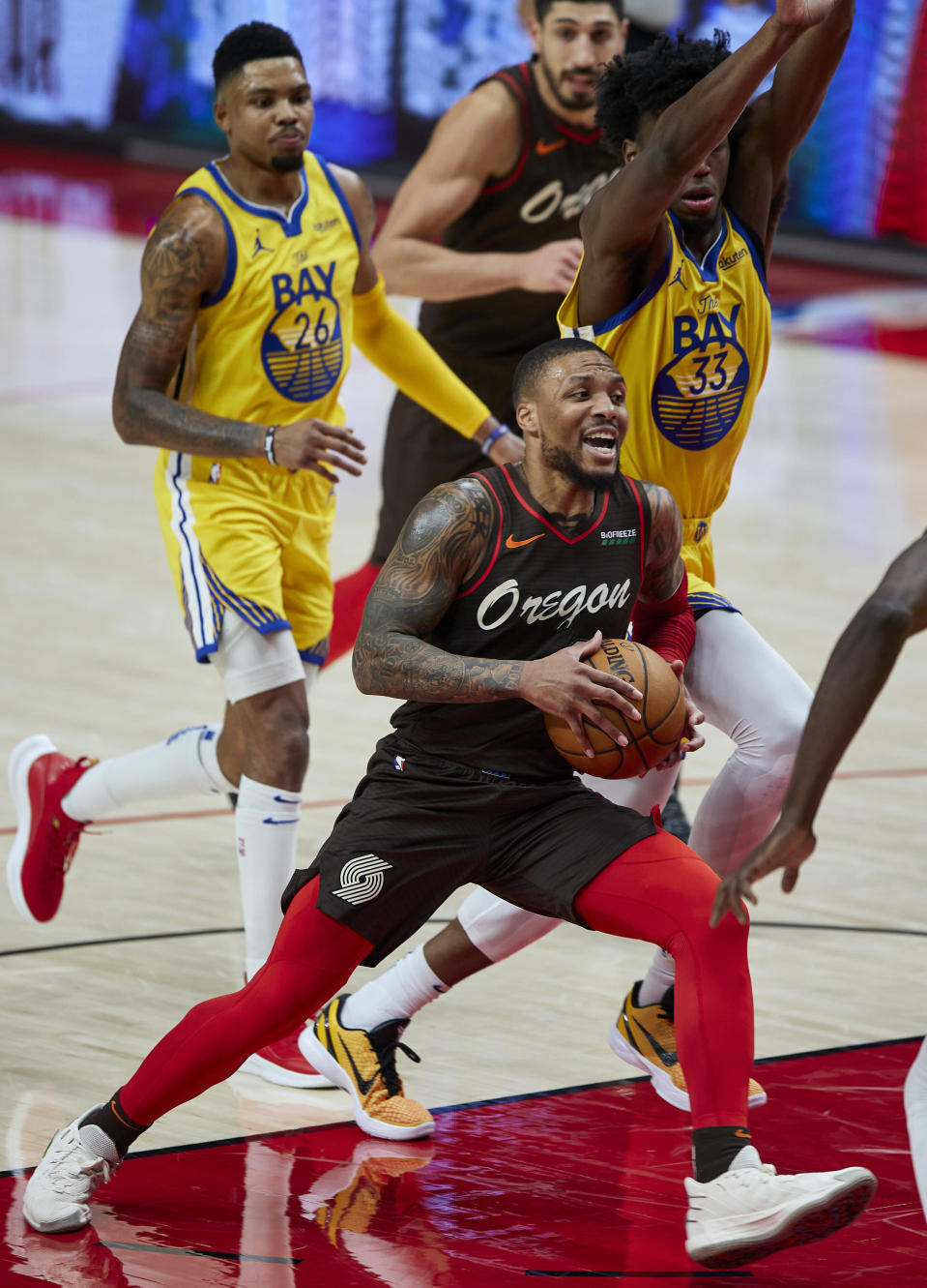 Portland Trail Blazers guard Damian Lillard drives to the basket in front of Golden State Warriors center James Wiseman, right, and forward Kent Bazemore during the second half of an NBA basketball game in Portland, Ore., Wednesday, March 3, 2021. (AP Photo/Craig Mitchelldyer)
