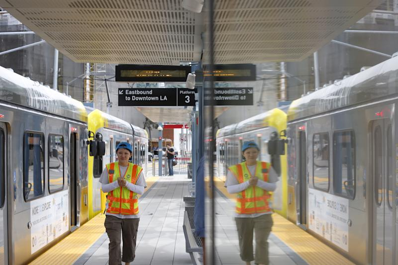 SANTA MONICA, CA - MAY 20: Anna Chen, PIO with MTA, walks past a train at the Metro Expo Line extension opens in Santa Monica on May 20, 2016. The 6.6 mile rail extension from Santa Monica to Culver City will provide L.A. County residents an alternative to the congested I-10 Santa Monica Freeway and offer a 48-minute train ride between Santa Monica and downtown Los Angeles. (Photo by Genaro Molina/Los Angeles Times via Getty Images)