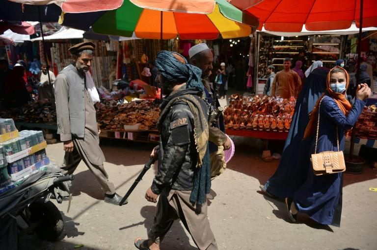 A woman looks back as a Taliban fighter (C) walks past shoppers along Mandawi market in Kabul on September 1, 2021 (AFP/HOSHANG HASHIMI)