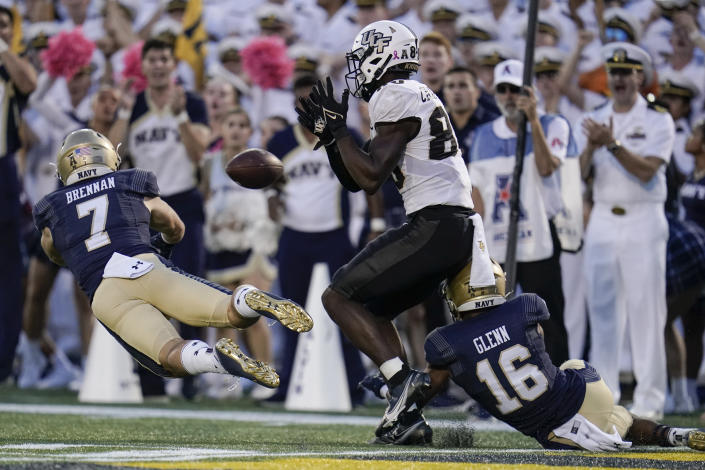 Navy safety Kevin Brennan (7) breaks up a pass intended for UCF wide receiver Nate Craig-Myers, center, as cornerback Jamal Glenn (16) helps defend during the second half of an NCAA college football game, Saturday, Oct. 2, 2021, in Annapolis, Md. Navy won 34-30. (AP Photo/Julio Cortez)