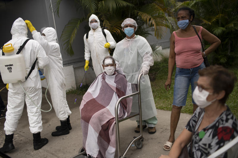 Army soldiers wearing protective gear prepare to disinfect the Marechal Hermes Urgent Care Unit, as patients wait outside for medical attention, amid the new coronavirus pandemic in Rio de Janeiro, Brazil, Wednesday, May 6, 2020. (AP Photo/Silvia Izquierdo)