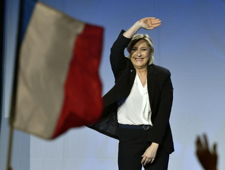 French presidential election candidate for the far-right Front National party Marine Le Pen waves as she arrives on stage to give a speech during a campaign meeting on April 2, 2017 at the Bordeaux-Lac exhibition center in Bordeaux, western France
