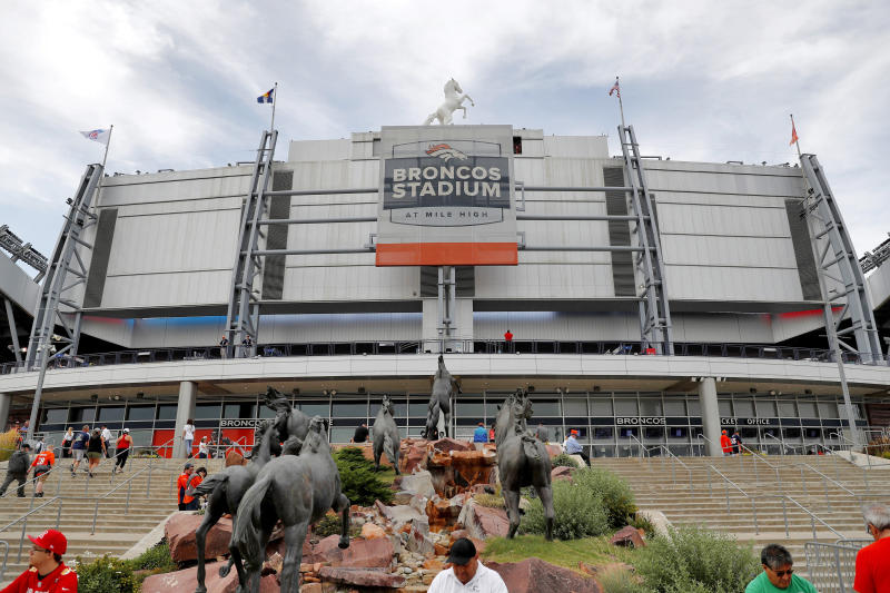 """FILE - In this Aug. 29, 2019, file photo, fans head into the Denver Broncos team store below the south scoreboard in Mile High Stadium before an NFL preseason football game between the Arizona Cardinals and the Broncos in Denver. The Broncos announced on Wednesday, Sept. 4, 2019, that they will partner with Colorado-based Empower Retirement on a 21-year deal to name the stadium """"Empower Field at Mile High."""" (AP Photo/David Zalubowski, File)"""