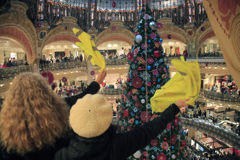 Demonstrators waves their yellow vest as they stage a protest at the Galeries Lafayette shopping mall in Paris, Sunday, Nov. 17, 2019. Yellow vest protesters staged new actions Sunday across France to mark the birth last year of their movement for economic justice, one day after scuffles between Paris police and activists marred the anniversary. (AP Photo/Michel Euler)