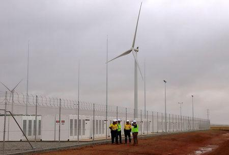 Officials and workers gather outside the compound housing the Hornsdale Power Reserve, featuring the world's largest lithium ion battery made by Tesla, during the official launch near the South Australian town of Jamestown, in Australia, December 1, 2017. REUTERS/David Gray