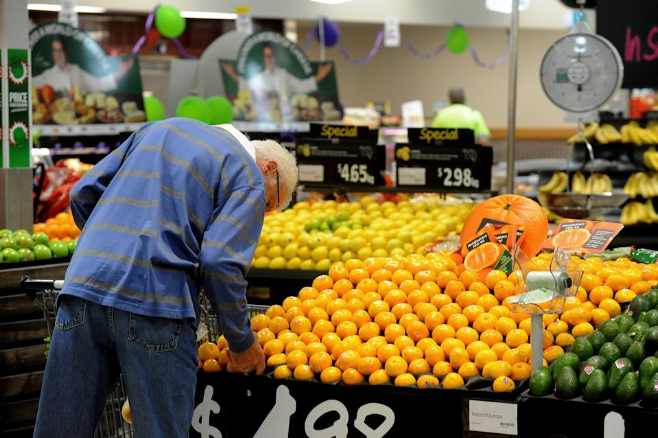 A shopper inspects fruit inside a Woolworths grocery store in Brisbane.