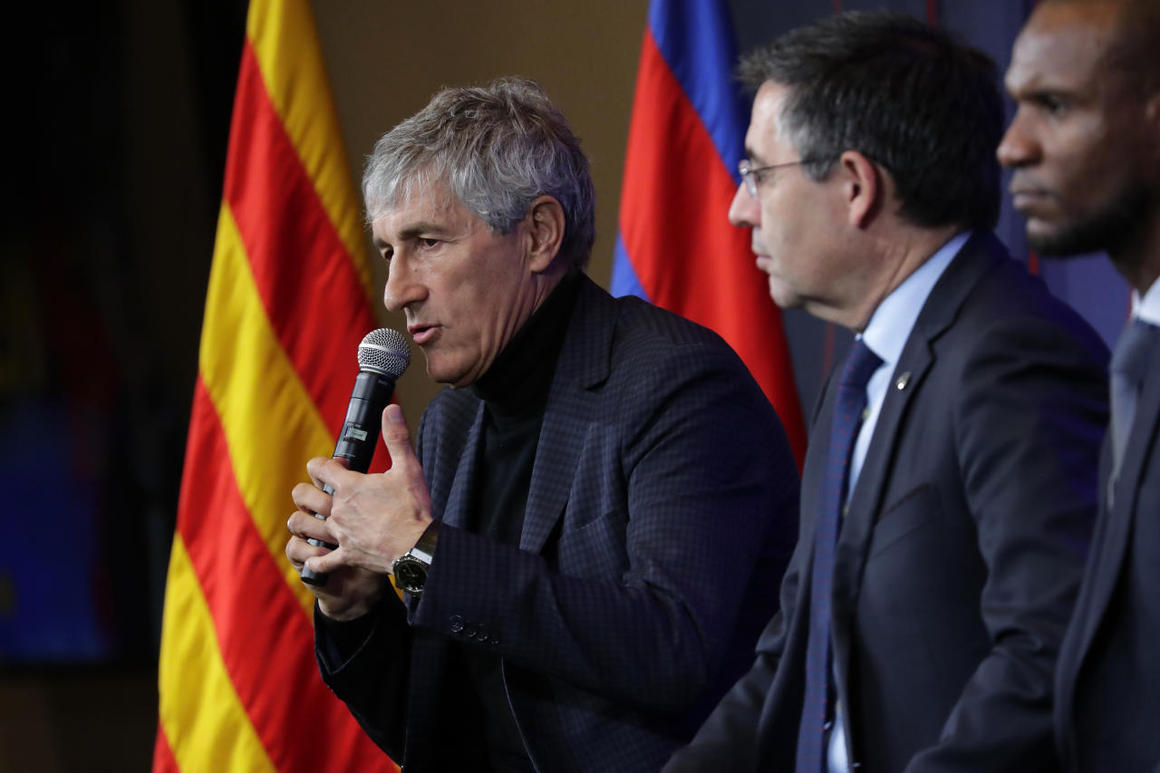 Soccer coach Quique Setien answers journalists during a news conference with FC Barcelona's President Josep Maria Bartomeu, center, and director of football Eric Abidal, right, after being officially introduced as the club's new coach at the Camp Nou stadium in Barcelona, Spain, Tuesday, Jan. 14, 2020. Barcelona made a rare coaching change midway through the season, replacing Ernesto Valverde with former Real Betis manager Quique Setien on Monday. (AP Photo/Emilio Morenatti)