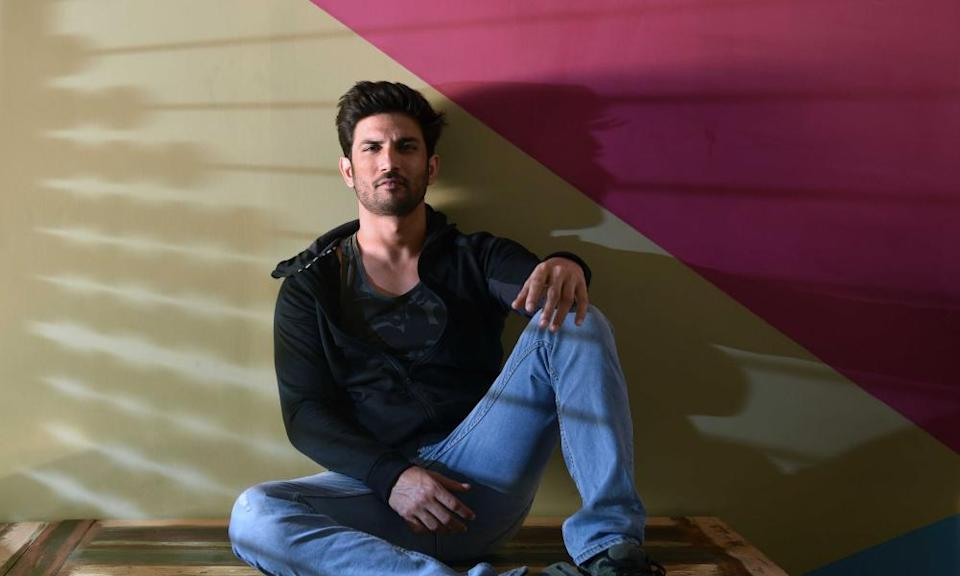Portrait of Sushant Singh Rajput photographed sitting against a multicoloured wall