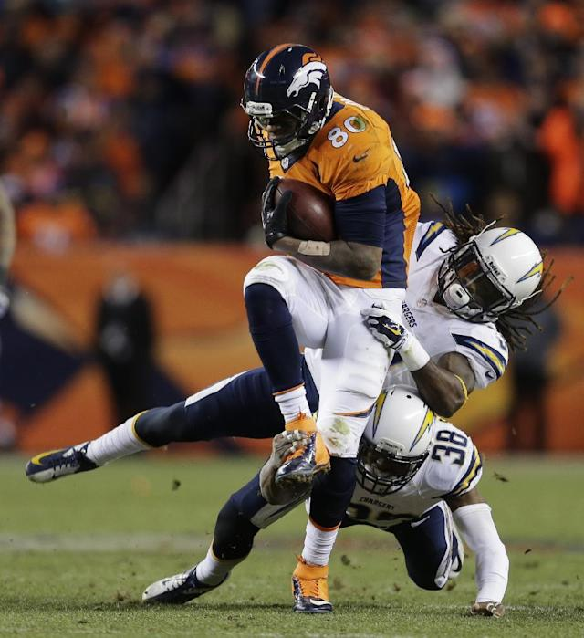 Denver Broncos tight end Julius Thomas (80) is pulled down by San Diego Chargers defensive back Jahleel Addae (37) and San Diego Chargers strong safety Marcus Gilchrist (38) in the fourth quarter of an NFL AFC division playoff football game, Sunday, Jan. 12, 2014, in Denver. (AP Photo/Joe Mahoney)