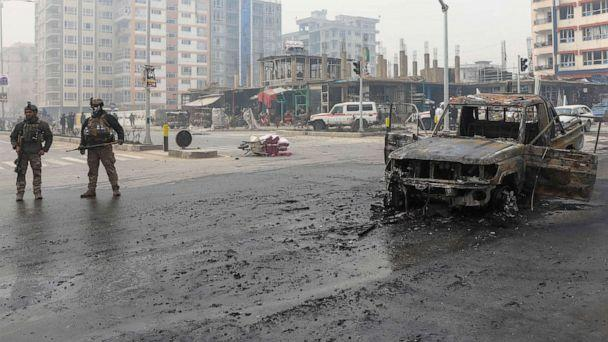PHOTO: A charred vehicle sits in the road as Afghan security forces inspect the site of a bomb explosion in Kabul, Afghanistan, Dec. 20, 2020. (Hedayatullah Amid/EPA via Shutterstock)