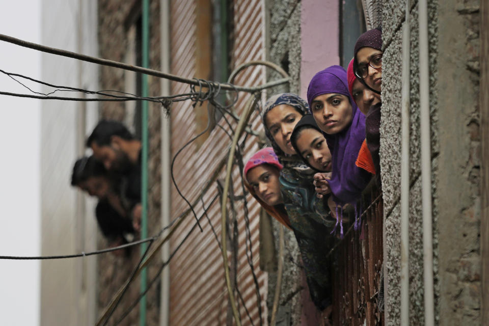 Indian Muslim women look out of a window as security officers patrol a street in New Delhi, India, Wednesday, Feb. 26, 2020. At least 20 people were killed in three days of clashes in New Delhi, with the death toll expected to rise as hospitals were overflowed with dozens of injured people, authorities said Wednesday. The clashes between Hindu mobs and Muslims protesting a contentious new citizenship law that fast-tracks naturalization for foreign-born religious minorities of all major faiths in South Asia except Islam escalated Tuesday. (AP Photo/Altaf Qadri)