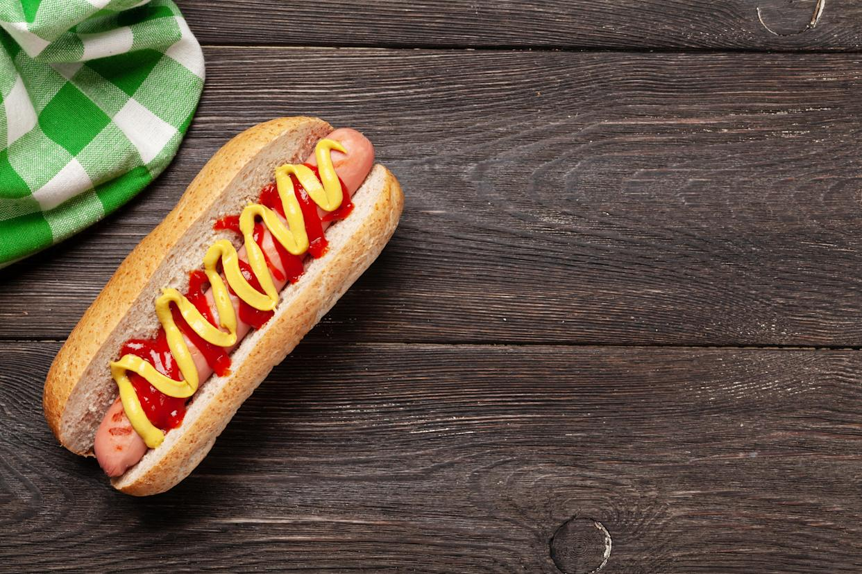 Hot dog with mustard and ketchup on wooden background. Top view with copy space. Flat lay
