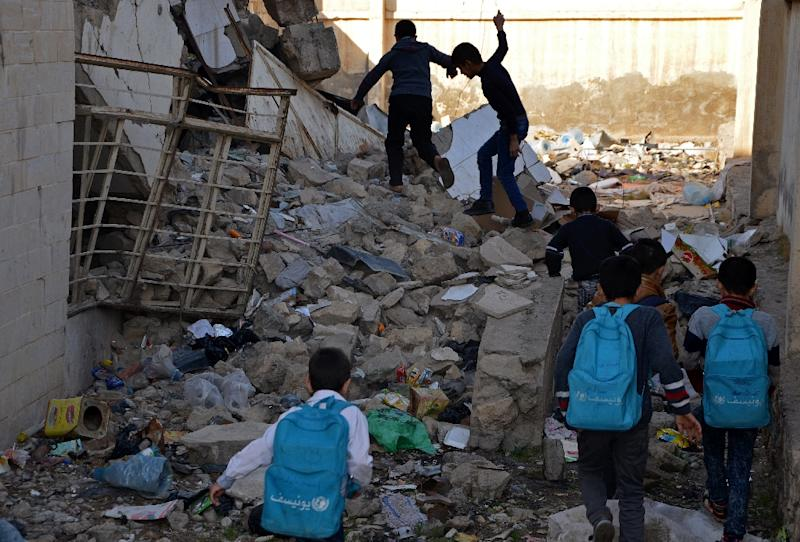 Iraqi children walk in rubble as they head to school in the battered city of Mosul on December 27, 2017 Through games, mime and sport, an instructor aims to help show the teachers -- some of whom are themselves traumatised -- how best to handle students struggling to cope with the mental scares of the Islamic State group rule and the fighting that ended it. (AFP Photo/Ahmad MUWAFAQ)