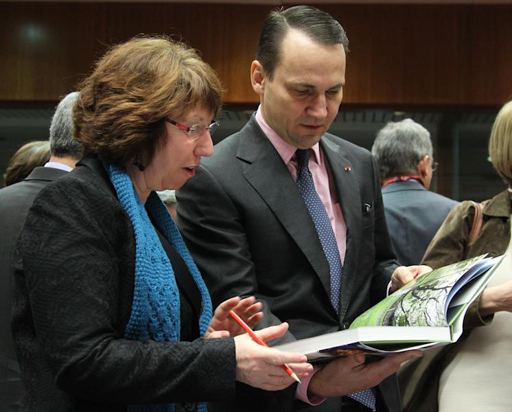 EU foreign policy chief Catherine Ashton, left, looks at a book written by the wife of Poland's Foreign Minister Radoslaw Sikorski, during the EU foreign ministers meeting, at the European Council building in Brussels, Monday, Feb. 18, 2013. European Union foreign ministers were set Monday for a showdown over the bloc's arms embargo on Syria, while tighter sanctions on North Korea were expected to get waved through. (AP Photo/Yves Logghe)