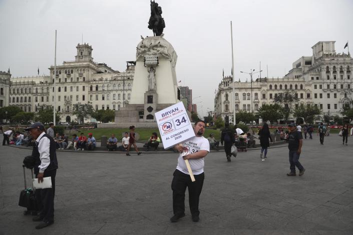 """In this Dec. 13, 2019 photo, congressional candidate Bryan Russell campaigns at San Martin Plaza in Lima, Peru. The purpose of politicking, he said, is to """"break the paradigm"""" that people with Down syndrome can't be independent. (AP Photo/Martin Mejia)"""