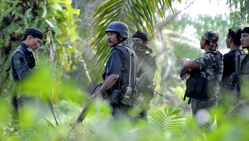 In this picture taken on March 2, 2013, a group of Malaysian police commandos stand guard near the area where the stand-off with Filipino gunmen took place in Tanduo village, Lahad Datu, Sabab , Malaysia. Gunmen ambushed and killed five Malaysian policemen as fears mounted that armed intruders from the southern Philippines had slipped into at least three coastal districts on Borneo island, officials said Sunday. (AP Photo/Bernama News Agency) MALAYSIA OUT, NO SALES, NO ARCHIVE