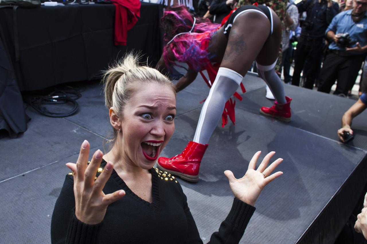 "A woman reacts as people take part in ""TWERKERS"", an event organised to break the Guinness World Record for largest number of people to perform a dance known as ""twerking"", in New York, September 25, 2013. REUTERS/Eduardo Munoz (UNITED STATES - Tags: SOCIETY ENTERTAINMENT)"