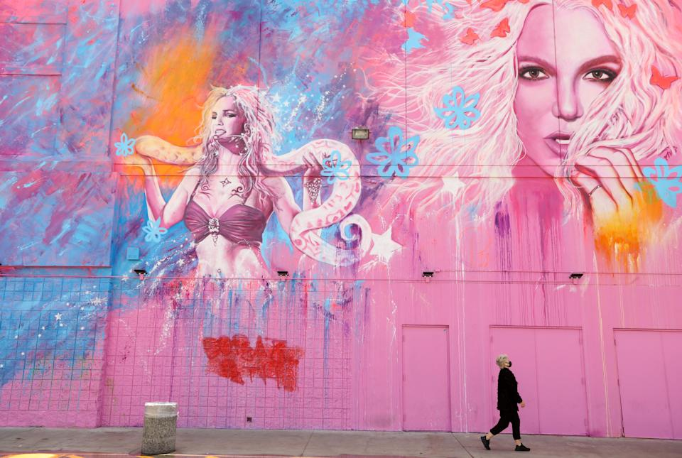 A woman, masked against COVID-19, walks past a building that features the image of Britney Spears at a shopping center in the Fairfax District in Los Angeles on May 18, 2020. (Genaro Molina / Los Angeles Times via Getty Images)