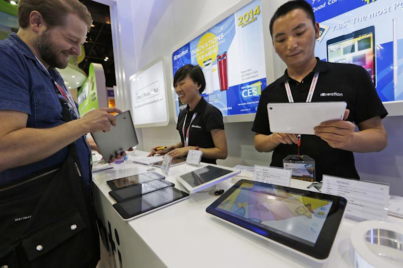 In this April 12, 2014 photo, staff members show the Chinese made tablets to a buyer in a booth at the Global Sources Spring China Sourcing Fair in Hong Kong. As China's economy downshifts, manufacturers are bracing for the turning point that's in store for the world's second biggest economy. (AP Photo/Kin Cheung)