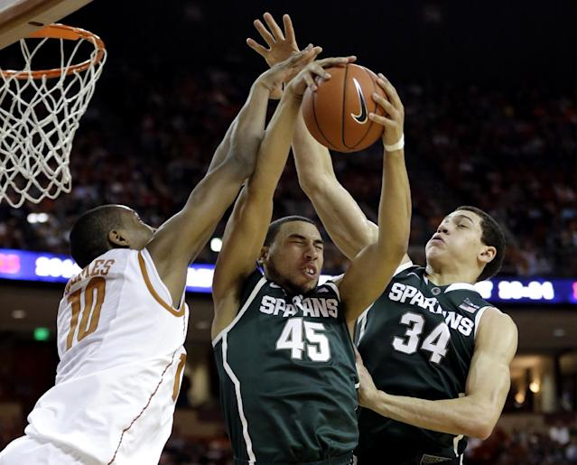 Michigan State's Denzel Valentine (45) pulls in a rebound between teammate Gavin Schilling (34) and Texas' Jonathan Holmes (10) during the first half of an NCAA college basketball game, Saturday, Dec. 21, 2013, in Austin, Texas. (AP Photo/Eric Gay)