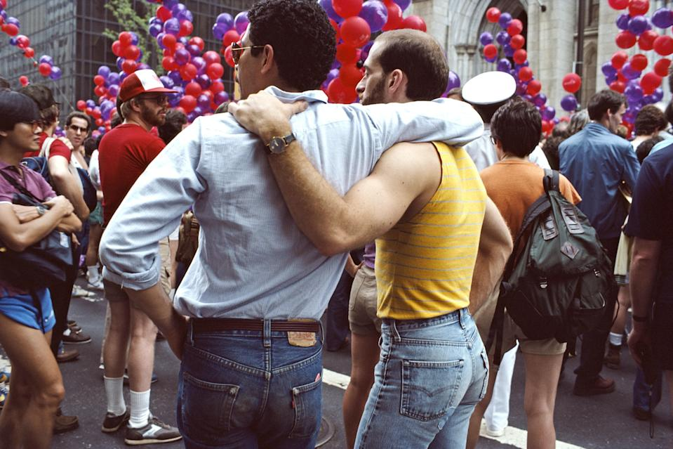 "Two men watch the <a href=""https://www.cntraveler.com/gallery/new-york-city-lgbtq-guide?mbid=synd_yahoo_rss"" rel=""nofollow noopener"" target=""_blank"" data-ylk=""slk:Gay Pride Parade"" class=""link rapid-noclick-resp"">Gay Pride Parade</a> in 1984. The first celebration, now held every year in June, took place in 1970; it followed on the heels of the 1969 riots at Stonewall Inn, which launched the modern movement for LGBTQ+ rights."