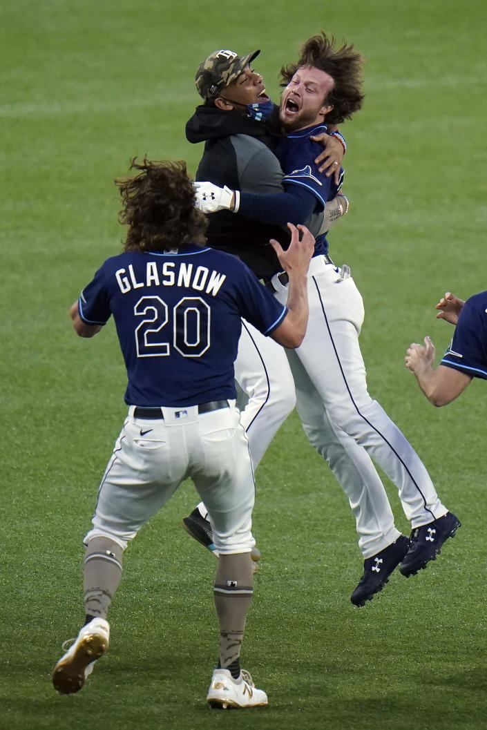 Tampa Bay Rays' Brett Phillips, right, celebrtes with teammates, including Tyler Glasnow after his walk-off RBI single off New York Mets relief pitcher Aaron Loup scored Brandon Lowe during the ninth inning of a baseball game Friday, May 14, 2021, in St. Petersburg, Fla. (AP Photo/Chris O'Meara)
