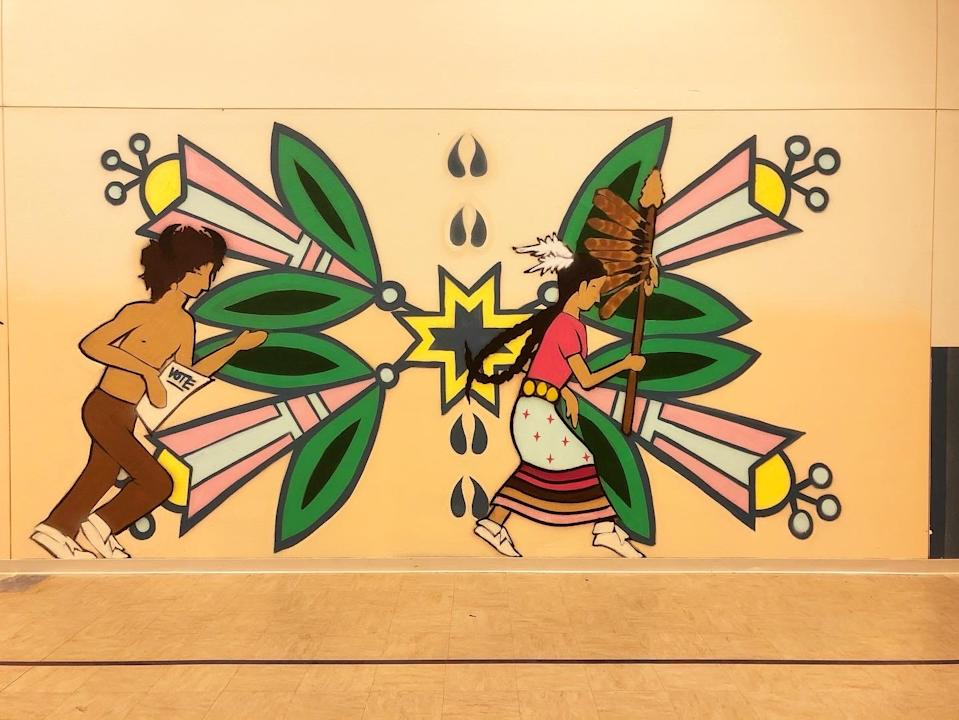 A mural features running Native American youths, one of them carrying a paper urging the viewer to vote. The mural, painted by artist Jeremy Fields, is one of many painted by Fields urging tribal members across the nation to engage on Election Day. This mural is located on the Standing Rock Indian Reservation in Wakpala, S.D.
