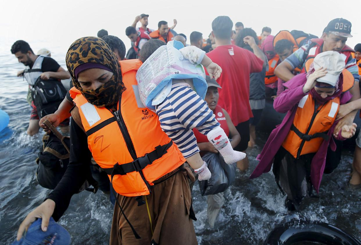 Syrian refugee mother carries her child off a dinghy after arriving at a beach on the Greek island of Lesbos after crossing a part of the Aegean Sea from Turkey September 18, 2015.