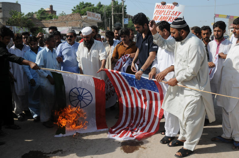 Pakistani protesters burn representations of US and Indian flags  at an anti-American rally in Multan, Pakistan on Friday, Sept 23, 2011. Pakistan lashed out at the U.S. for accusing the country's most powerful intelligence agency of supporting extremist attacks against American targets in Afghanistan _ the most serious allegations against Islamabad since the beginning of the Afghan war. (AP Photo/Khalid Tanveer)