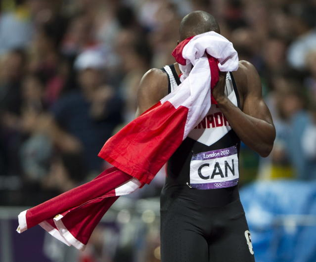 Canada's Oluseyi Smith cries into a flag after the Canadian relay team had their third place finish disqualified in the men's 4x100 metre final at the 2012 Summer Olympics in London, Saturday, August 11, 2012.THE CANADIAN PRESS/Ryan Remiorz