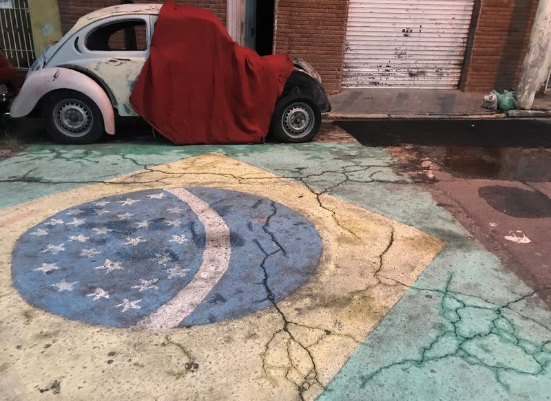 A Brazilian flag is seen painted on a street in front of a Volkswagen Beetle car in Sao Paulo