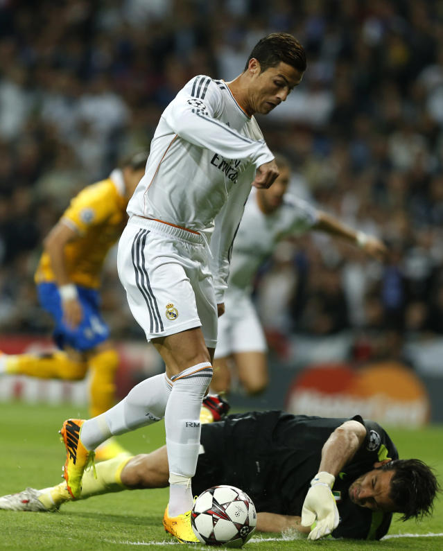 Real's Cristiano Ronaldo takes the ball past Juventus goalkeeper Gianluigi Buffon before scoring his side's first goal during a Group B Champions League soccer match between Real Madrid and Juventus at the Santiago Bernabeu stadium in Madrid, Spain, Wednesday Oct. 23, 2013. (AP Photo/Andres Kudacki)