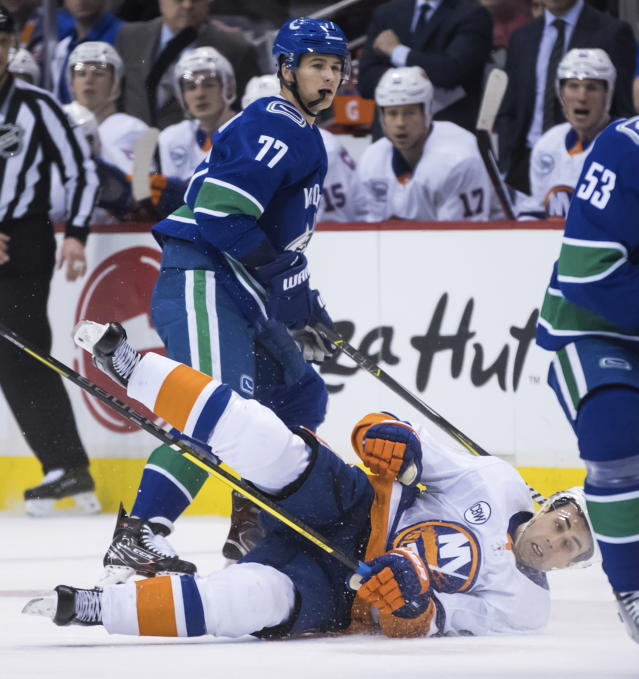 New York Islanders' Jordan Eberle, front, falls to the ice after being checked by Vancouver Canucks' Nikolay Goldobin, of Russia, during the first period of an NHL hockey game Saturday, Feb. 23, 2019, in Vancouver, British Columbia. (Darryl Dyck/The Canadian Press via AP)