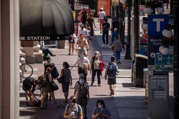 People are seen walking down a sidewalk in downtown Vancouver, British Columbia on Tuesday, June 22, 2021 wearing face masks to protect against the spread of COVID-19. (Ben Nelms/CBC - image credit)
