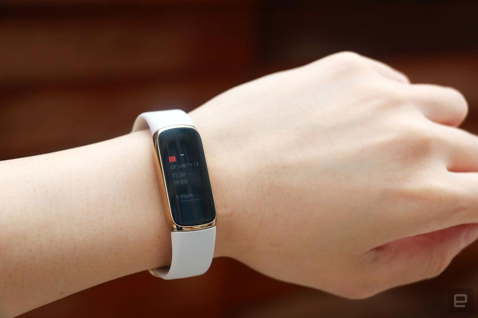 <p>Slightly off angle view of the Fitbit Luxe with a light pink silicone band on a wrist against a dark brown background. The screen shows a calendar notification for an event from 5:30pm to 7pm.</p>