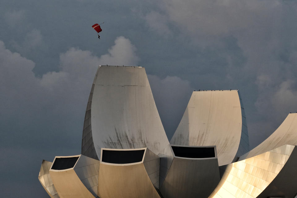 A member of the Red Lions parachute team is pictured with the ArtScience Museum as he prepares to land during the 56th National Day Parade rehearsal in Singapore on August 11, 2021 in Singapore. (Photo by Suhaimi Abdullah/NurPhoto via Getty Images)