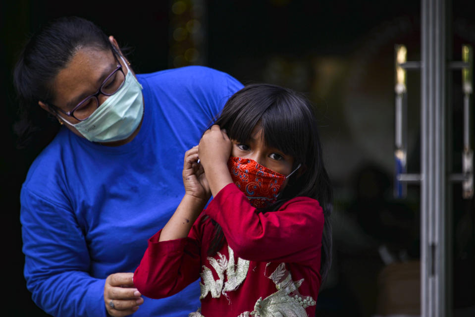 A volunteer gives a face mask to a child, amid concerns of the COVID-19 coronavirus, in Banda Aceh on April 7, 2020. (Photo by CHAIDEER MAHYUDDIN / AFP) (Photo by CHAIDEER MAHYUDDIN/AFP via Getty Images)