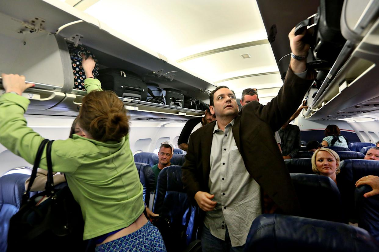 Passengers aboard a US Airways flight take their baggage from the overhead bin as they depart the plane in Phoenix, AZ on Oct. 7, 2013.