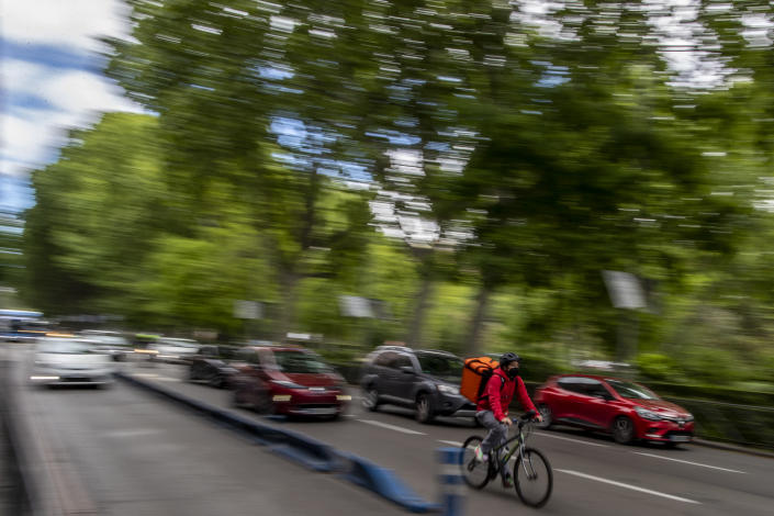 A delivery worker rides his bike in Madrid, Spain, Tuesday, May 11, 2021. Spain has approved a pioneering law that gives delivery platforms a mid-August deadline to hire the workers currently freelancing for them and that requires transparency of artificial intelligence to manage workforces. (AP Photo/Manu Fernandez)