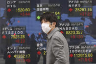 A man walks by an electronic stock board of a securities firm in Tokyo, Wednesday, Dec. 18, 2019. Asian shares were mostly higher Wednesday after record highs on Wall Street amid investor optimism about an interim U.S.-China trade deal announced last week. (AP Photo/Koji Sasahara)