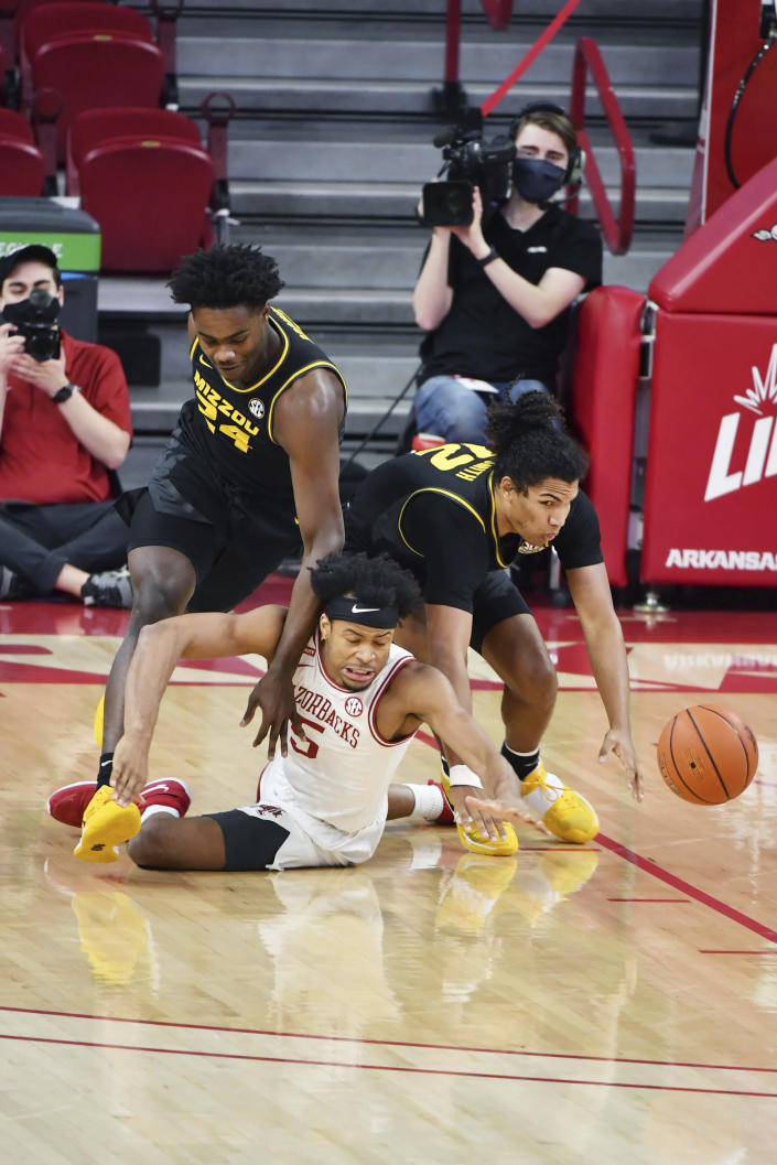 Arkansas forward Moses Moody (5) and Missouri's Kobe Brown (24) and Dru Smith (12) fight for a loose ball during the first half of an NCAA college basketball game in Fayetteville, Ark. Saturday, Jan. 2, 2021. (AP Photo/Michael Woods)
