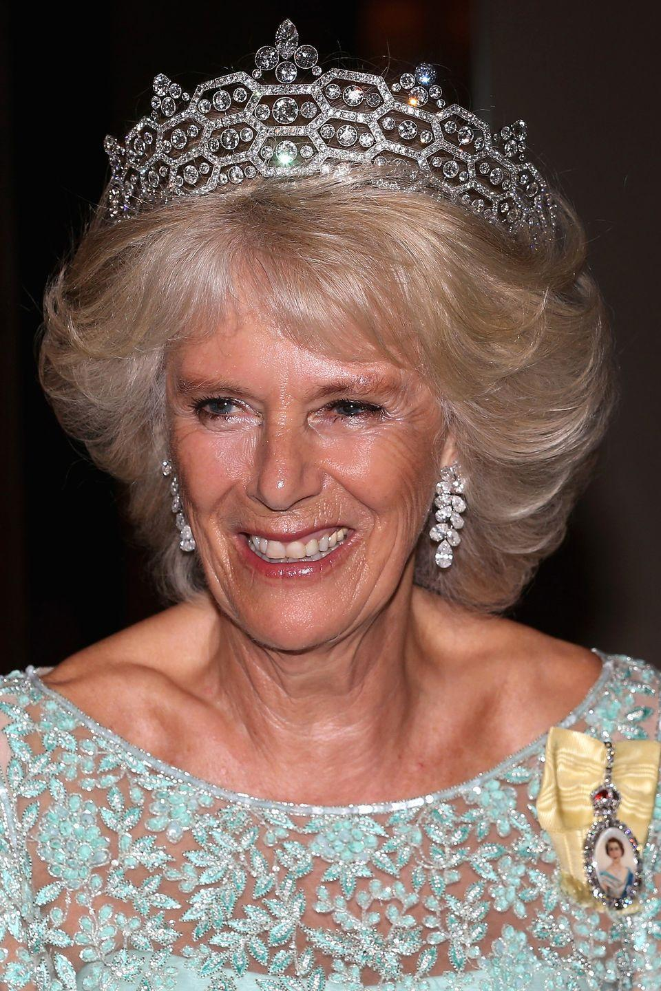 <p>The Greville tiara was made by Boucheron for Dame Margaret Helen Greville in 1920. It is also known as the Boucheron Honeycomb tiara, and is worn here by Camilla, Duchess of Cornwall. Greville left the tiara to the Queen Mother when she died in 1942, and upon the death of the Queen Mother in 2002, the Queen inherited the headpiece. It is now one of three tiaras on long-term loan to Camilla, who married Prince Charles in 2005. </p>