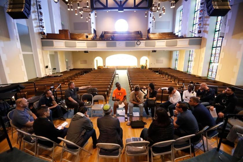 SAN FRANCISCO, CA - SEPTEMBER 11, 2019 - - Carl Patterson, center, in orange t-shirt, talks about his experience living on the streets homeless to participants of GLIDEÕs, ÒOfficer and a Mensch,Ó program in the sanctuary of GLIDE Church in San Francisco on September 11, 2019. The program tries to instill a greater understanding between law enforcement and the people of historically oppressed communities. Participants had a full immersion experience dealing with homelessness, addiction, mental illness, poverty and despair in the program. This training is intended to help leaders explore their understanding of the ways traditional government organizations and community-based providers can better ÒserveÓ challenged communities together to improve the quality of life for all of our citizens. (Genaro Molina / Los Angeles Times)