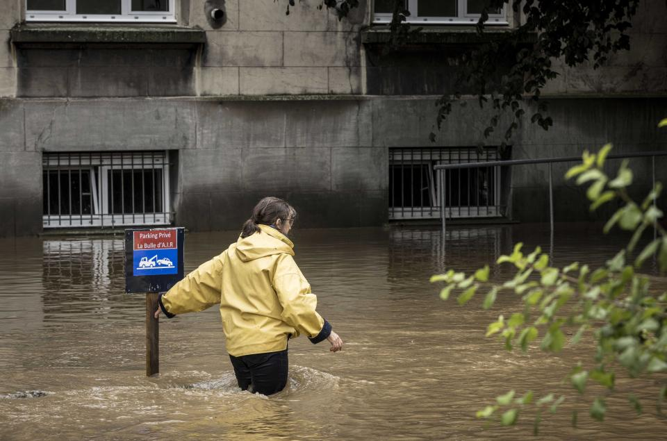 A woman braves the floodwaters in Liège, Belgium on Thursday.